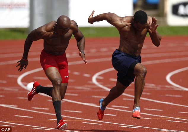 Tyson Gay, right, warms up alongside 100-meter relay runner Trell Kimmons